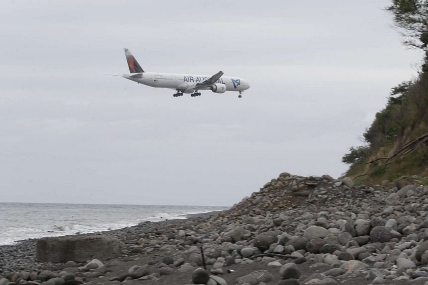 An airplane flying over a beach on the French Indian Ocean island of Reunion