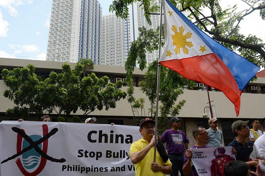 Anti-China protesters display the national flag during a protest in front of the Chinese consulate in the financial district of Manila on July 24, 2015.