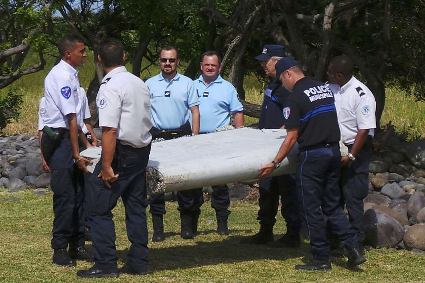 French gendarmes and police carry a large piece of plane debris which was found on the beach in Saint-Andre, on the French Indian Ocean island of La Reunion, in this picture taken July 29, 2015.