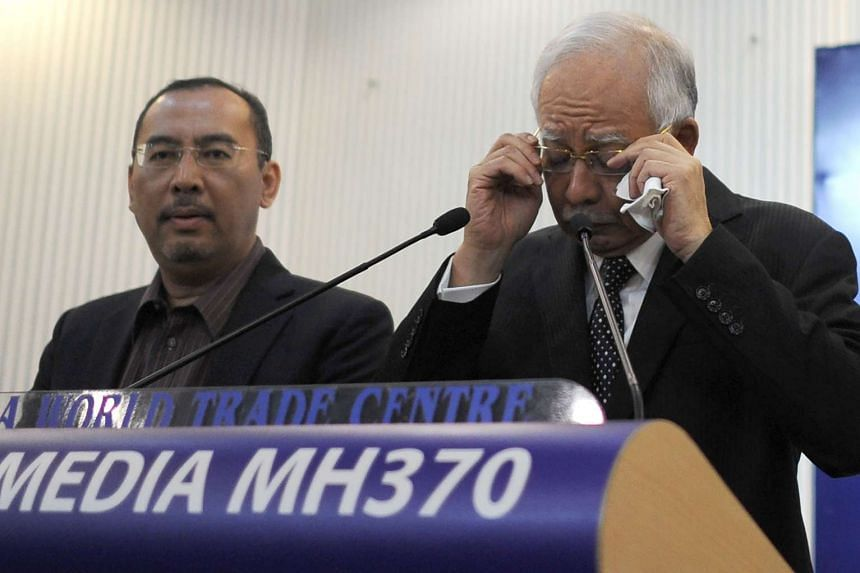 This picture taken early on August 6, 2015 shows Malaysia's Prime Minister Najib Razak (right) adjusting his glasses before delivering a statement during a press conference on the missing Malaysia Airlines flight MH370.