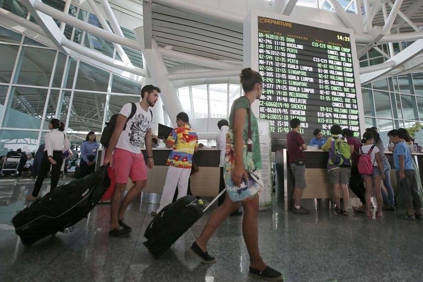 Passangers wait at Bali's Ngurah Rai International Airport after their flights were delayed because of volcanic activity from Mt Raung, in Bali, Indonesia, on Aug 6, 2015.