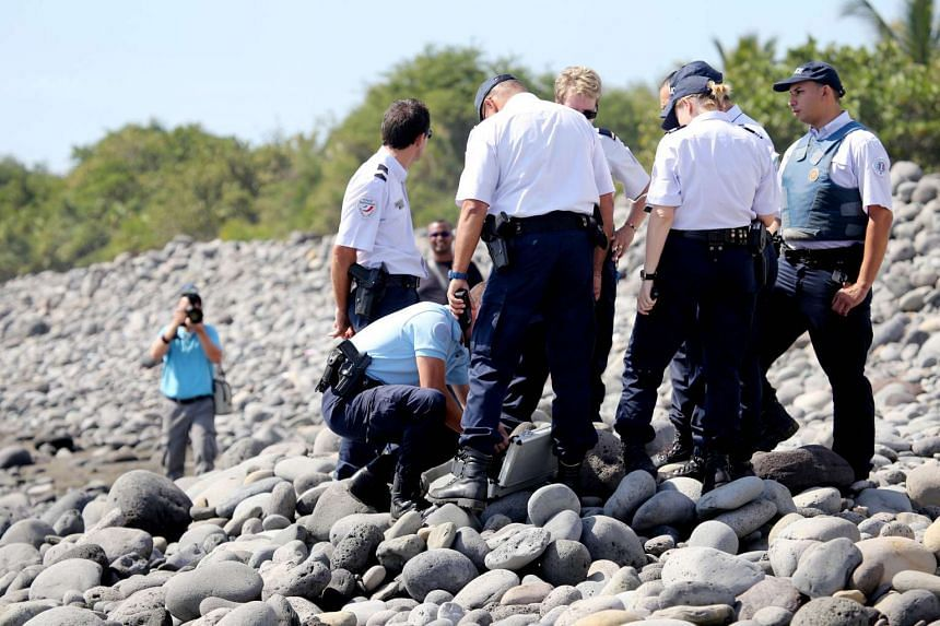 Police officers inspect metallic debris found on a beach in Saint-Denis on Reunion Island in the Indian Ocean on Aug 2, 2015.