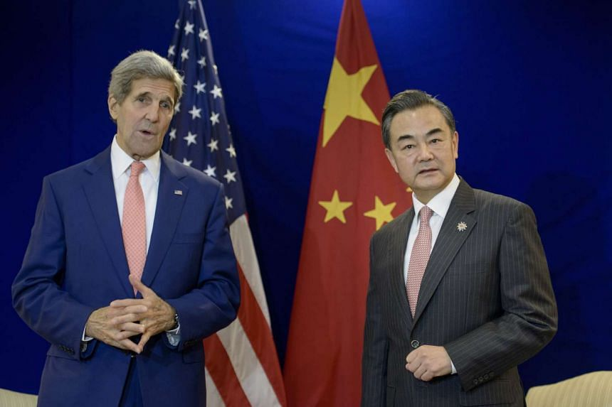 China's Foreign Minister Wang Yi (right) listens while US Secretary of State John Kerry talks before a bilateral meeting at the Putra World Trade Center in Kuala Lumpur on Aug 5, 2015.