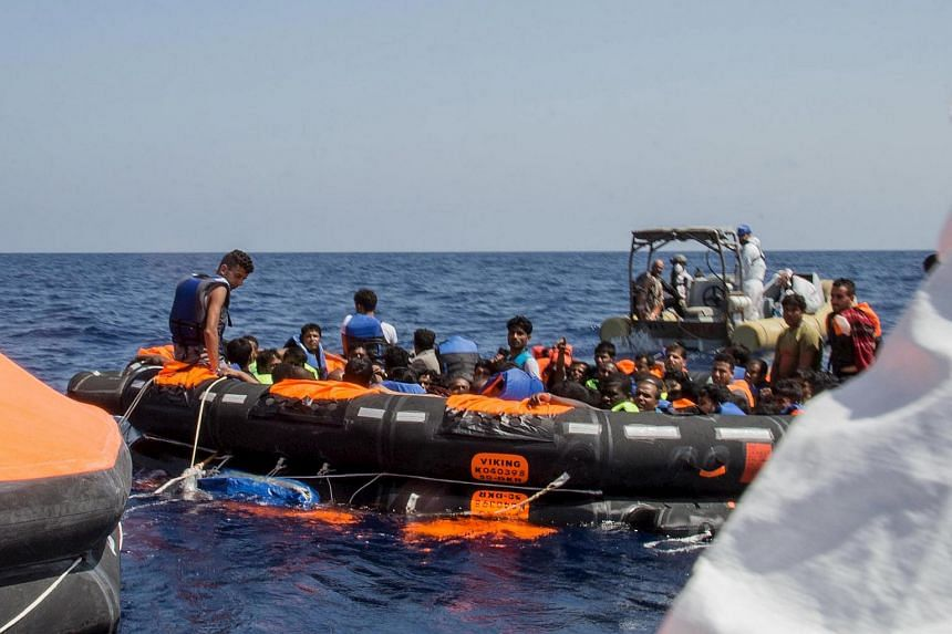 Surviving migrants are brought aboard Irish and Italian Navy life-boats in the area where their wooden boat capsized and sank off the coast of Libya on  Aug 5, 2015.