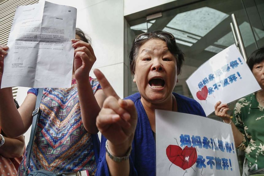 A relative of a passenger of Malaysia Airlines flight MH370 shouts her complaints outside the Malaysia Airlines office in Beijing, China, on Aug 6, 2015.