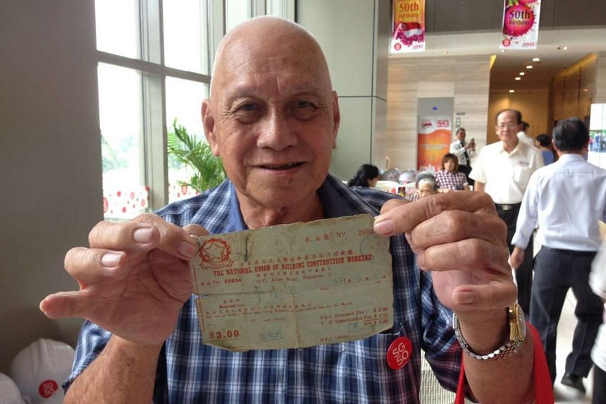 Driver Toh Keng Kee, 73, holding up his old union membership card. The former construction worker was one of the 17 pioneer builders honoured at MND's national day observance ceremony on Thursday.