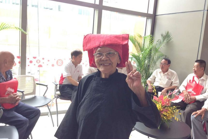 Madam Ng Moey Chye, 83, puts on her old samsui outfit. The former samsui woman was one of the 17 pioneer builders honoured at MND's national day observance ceremony on Thursday.
