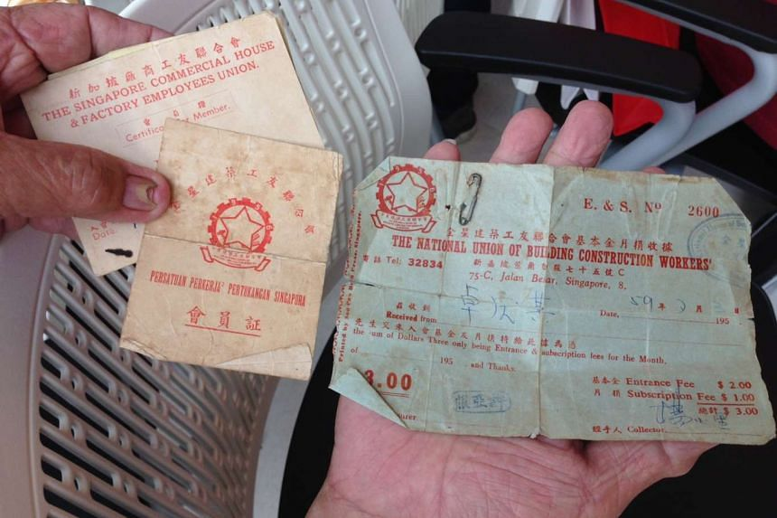 Former construction worker Toh Keng Kee displaying his old documents from back in the day.