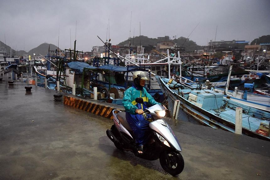 A man rides past fishing boats moored in a shelter at Nanfangao harbour in Yilan, Taiwan on Aug 6, 2015.