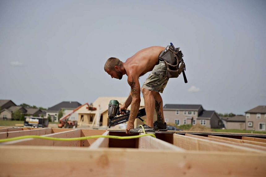 A contractor installs subfloor inside a house under construction for Ironwood Homes in Peoria, Illinois, U.S.