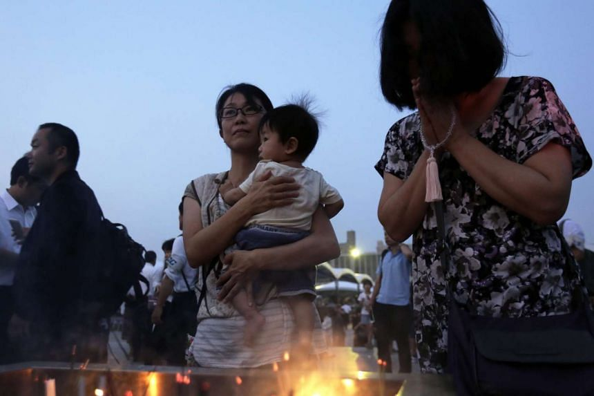 People offering prayers for victims of the atomic bombing during World War II in 1945, in front of a cenotaph at Hiroshima Peace Memorial Park in Hiroshima, Japan on Aug 6, 2015.