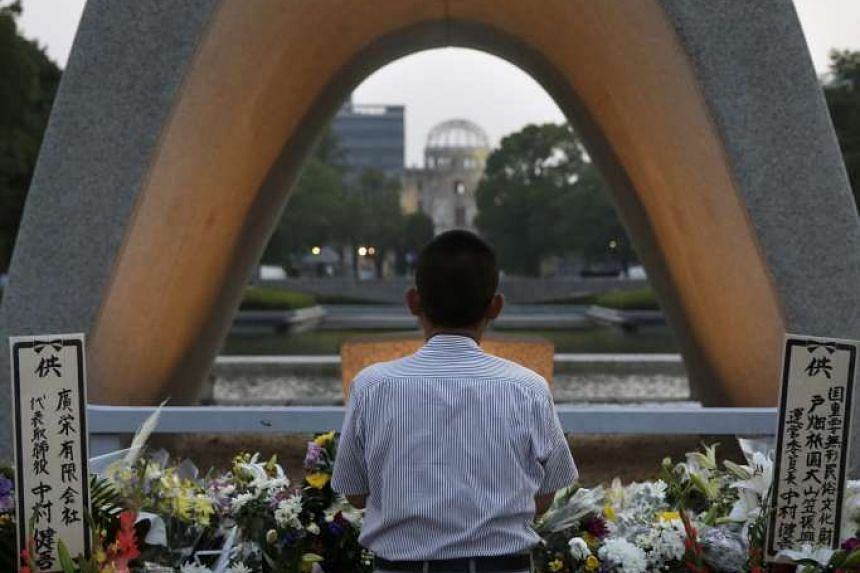 A man offering prayers for victims of the atomic bombing during World War II in 1945, in front of a cenotaph at Hiroshima Peace Memorial Park in Hiroshima, Japan on Aug 6, 2015.