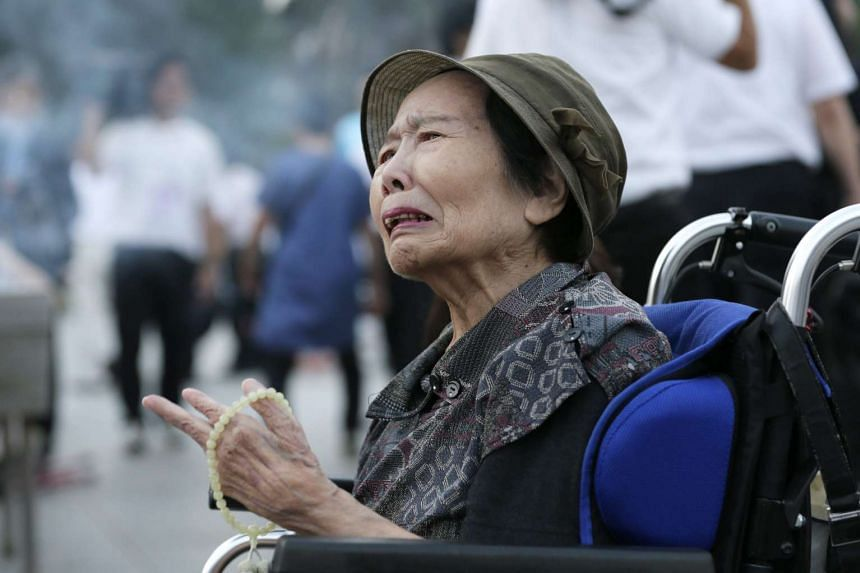 A Hiroshima resident cries as she is offering prayers for victims of the 1945 Hiroshima atomic bombing, in front of a cenotaph at the Hiroshima Peace Memorial Peace Park, in Hiroshima on Aug 6, 2015.