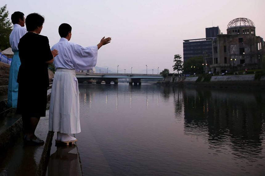 Shinto priests praying at the Motoyasu River opposite the Atomic Bomb Dome at sunrise in Hiroshima, western Japan on Aug 6, 2015.