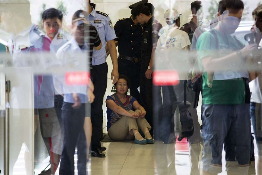 Relatives of passengers are stopped by police as they try to enter the building where the Malaysia Airlines office is located in Beijing, Aug 5, 2015.