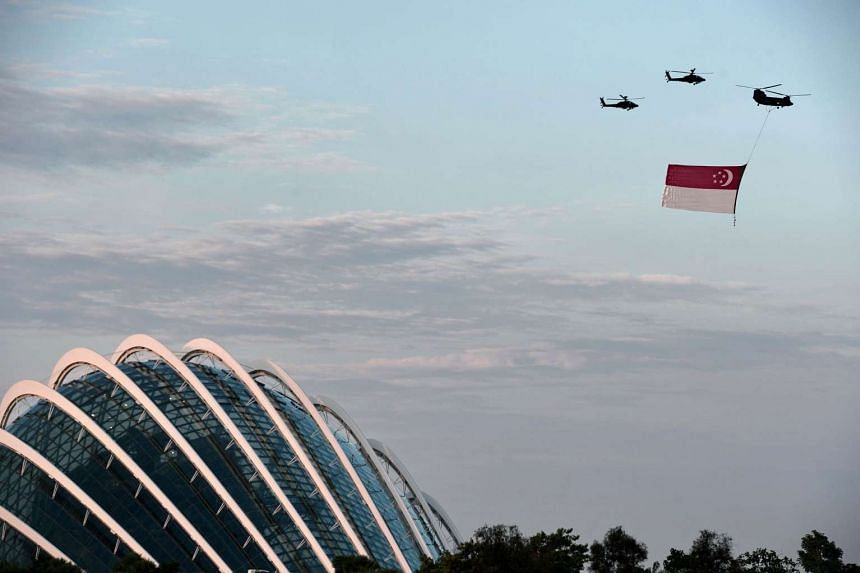 A Chinook helicopter (top right) from the Republic of Singapore Air Force flies a giant national flag over the Garden by the Bay dome during a preview for the 50th Singapore National Day celebration on Aug 1, 2015.