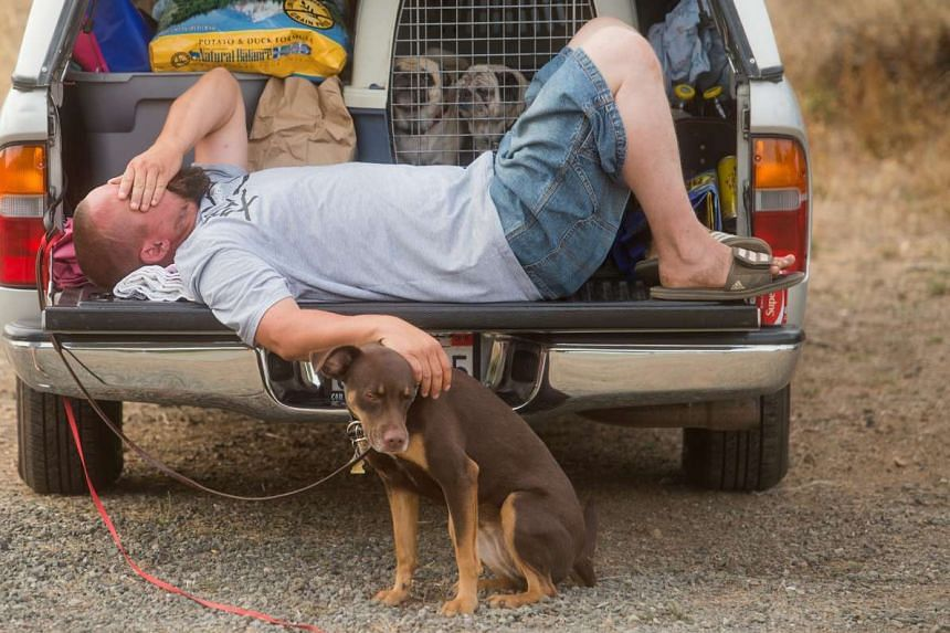 Mr Clayton Ingram, a Spring Valley resident whose community is under mandatory evacuation, resting at a designated evacuation area on Tuesday as the Rocky Fire burned homes near Clearlake Oaks. The week-old blaze has forced more than 13,000 people to