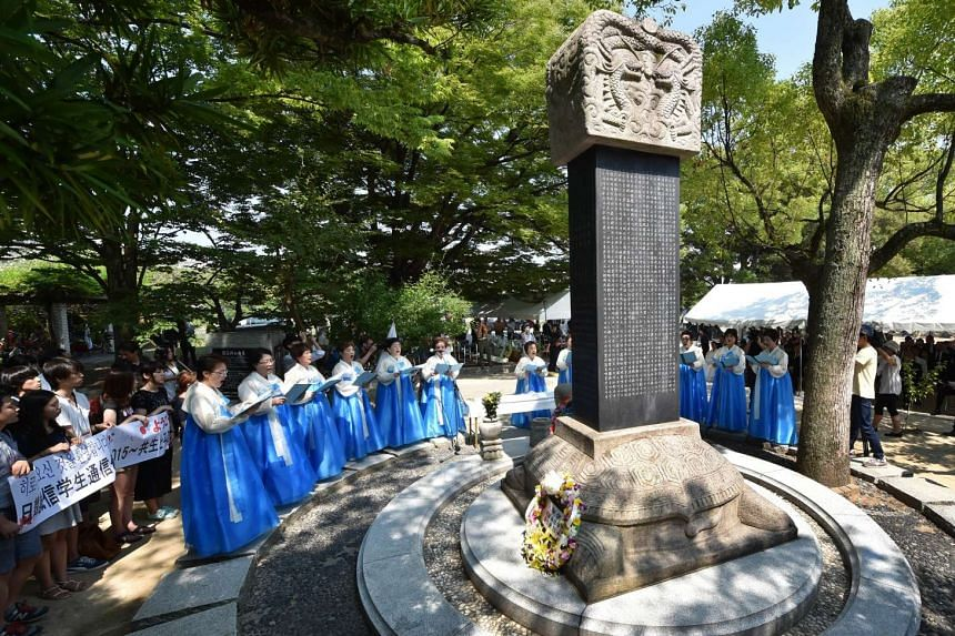 South Korean women praying for victims of the bombing at the Peace Memorial Park in Hiroshima.