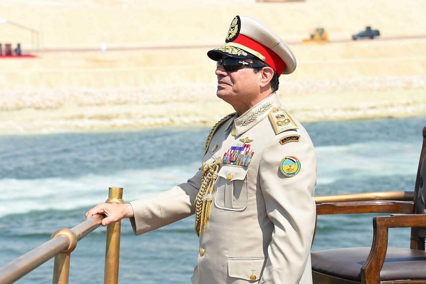 Egyptian President Abdel Fattah al-Sisi stands on a boat on the Suez Canal as he attends the celebration of an extension of the Suez Canal in Ismailia, Egypt on Aug 6, 2015.