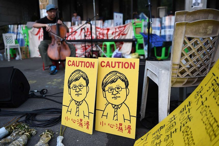 Two portraits of Taiwan Education Minister Wu Se-hwa are placed in front of the policemen during a demonstration at the Education Ministry in Taipei on Aug 5, 2015.