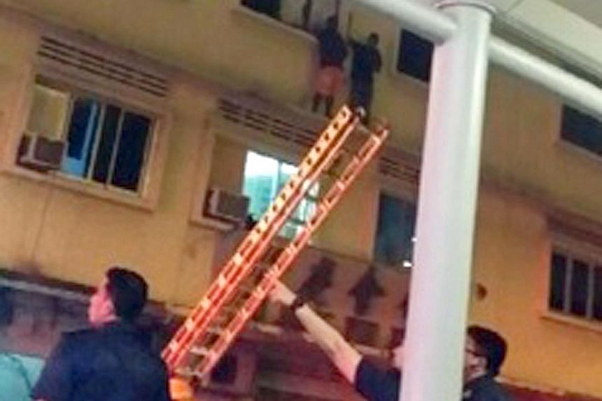 Two foreign workers awaiting rescue on the ledge outside the window of a house in Lorong 4 Geylang last December as a fire raged within. Four Malaysian cleaners died in the blaze.