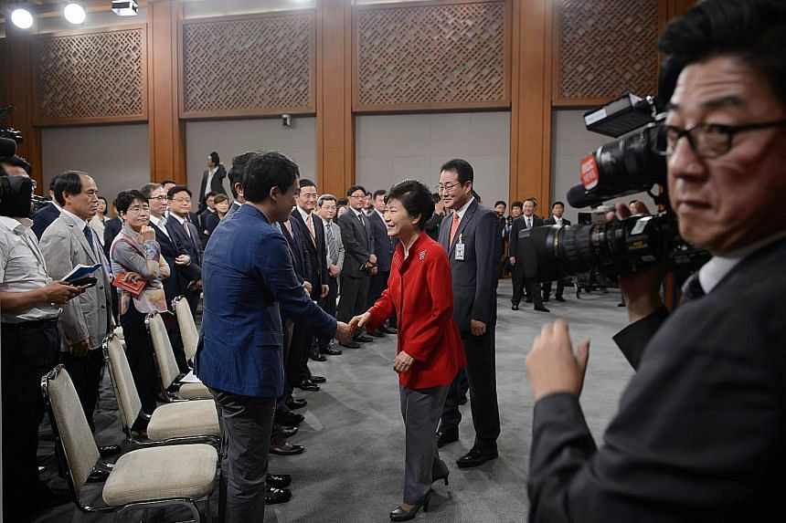 Ms Park Geun Hye with officials and audience members after delivering a speech at the presidential Blue House in Seoul yesterday. She urged workers to accept a proposed wage cap system, under which older workers swop an extended retirement age for fi