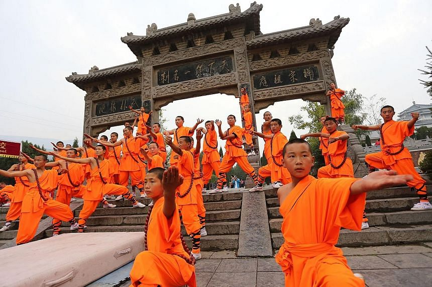Monks showing off their prowess during the Shaolin International Martial Arts Festival at Shaolin Temple last year. Temple abbot Shi Yongxin is known as China's CEO monk for transforming the monastery into a global commercial empire.