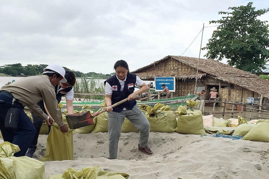 Singapore Red Cross member Charis Chan helping to fill sandbags to stave off flood waters in Nyaung Tone township, in Myanmar's Irrawaddy region. Severe floods have hit 12 of the country's 14 regions, leaving 74 dead and affecting more than 330,000 p