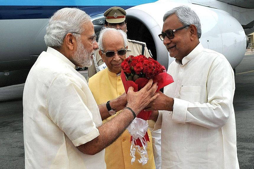 PM Narendra Modi (left) welcomed by Bihar Chief Minister Nitish Kumar upon Mr Modi's arrival in Patna, Bihar, on July 25. With them is Bihar Governor Keshari Nath Tripathi. Mr Modi's BJP alliance will face Mr Kumar's alliance in the state's elections