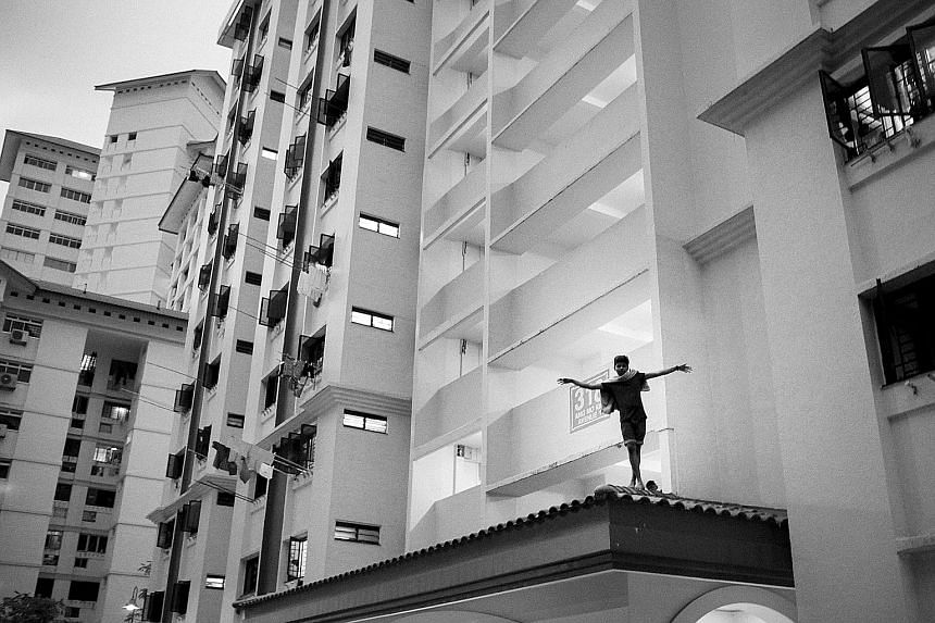 A boy walking on a ledge at a block of HDB flats in Ang Mo Kio from Bernice Wong's photo series School Of Hard Knocks. (Left above) A shot from Tay Kay Chin's photo series Made In Singapore, which traces the life of Bangladeshi foreign worker Salim J