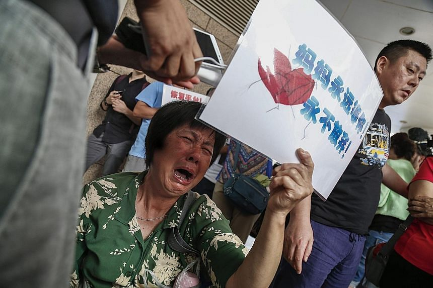 "A woman whose loved ones were on Flight MH370 in tears outside the Malaysia Airlines (MAS) office in Beijing yesterday. More than 20 family members of passengers held a protest outside the MAS office, accusing the airline of hiding the truth in a ""po"