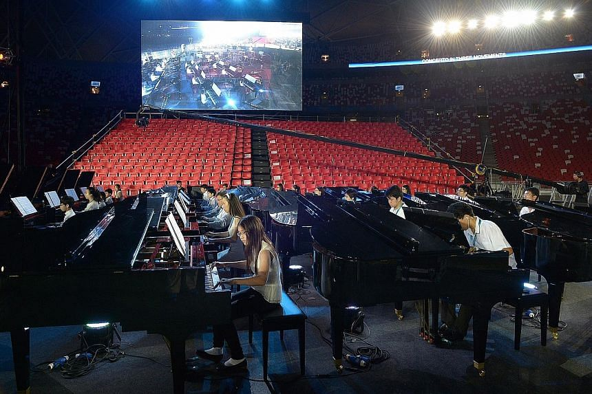 Some of the pianists, part of a contingent of 50 led by Chinese maestro Lang Lang, during rehearsals last night in preparation for the Sing50 concert tonight at the National Stadium. The musicians, aged seven to 52, will all play on 50 Steinway-desig