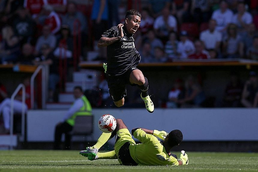 Liverpool's Roberto Firmino is airborne in an attempt to beat Swindon Town's Lawrence Vigouroux in a friendly on Aug 2. Firmino, who plays anywhere across the front three, will bring creativity and goals to the Reds.