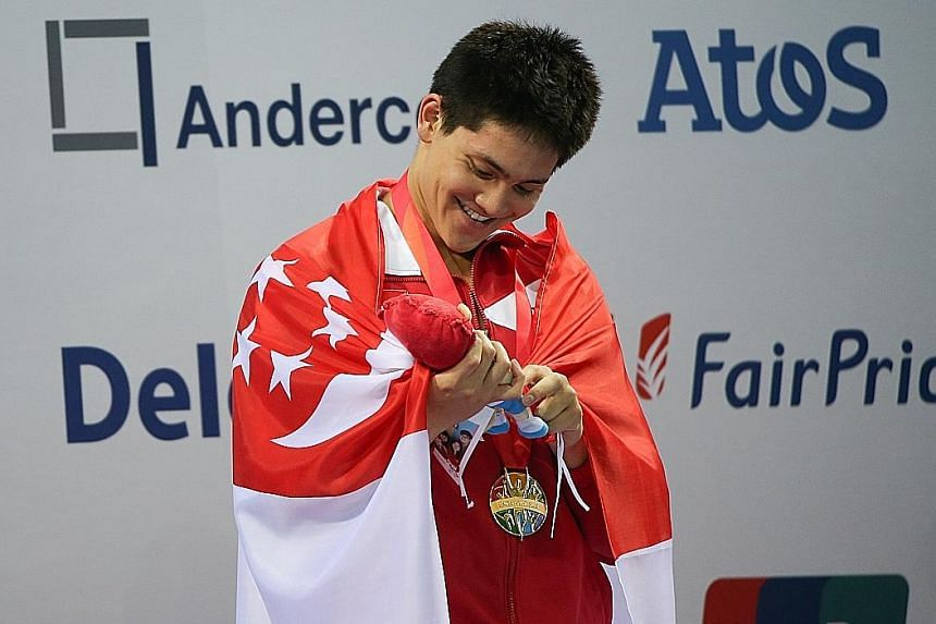 Joseph Schooling, now in Kazan for the world championships, admiring one of the Nila mascots received during his nine-gold SEA Games haul.