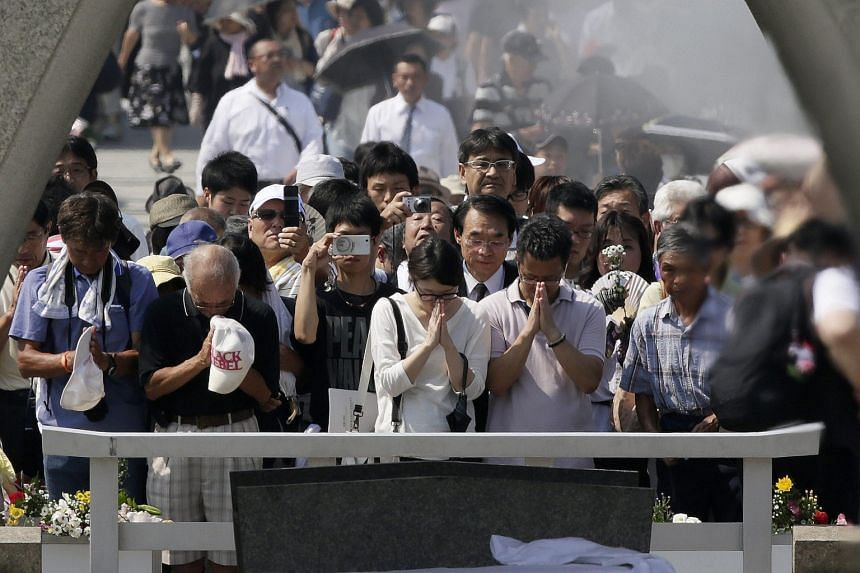 People praying at the Hiroshima Peace Memorial Park yesterday for the victims of the atomic bombing of the Japanese city 70 years ago.