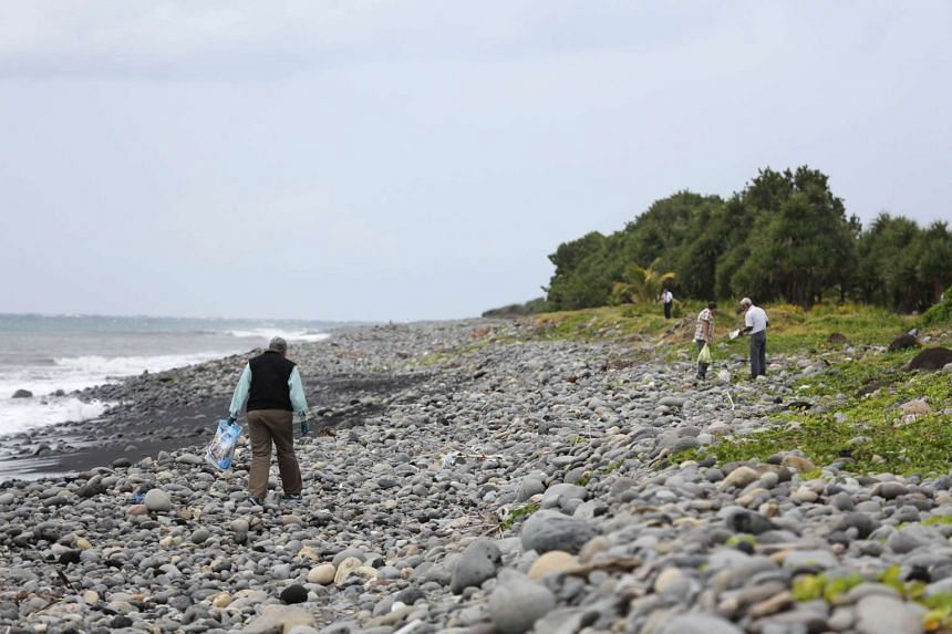 A Malaysian expert (left) looking for debris from Malaysia Airlines Flight MH370 on Reunion Island on Aug 4.