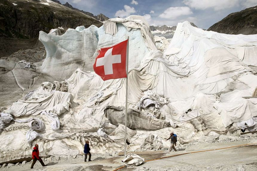 The Rhone glacier in the Swiss Alps on Aug 6, 2015, with the Swiss flag in the foreground.