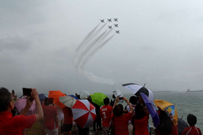 Families gathered along the coastline of Marina South to catch the Black Knights aerial display despite the intermittent heavy downpour.