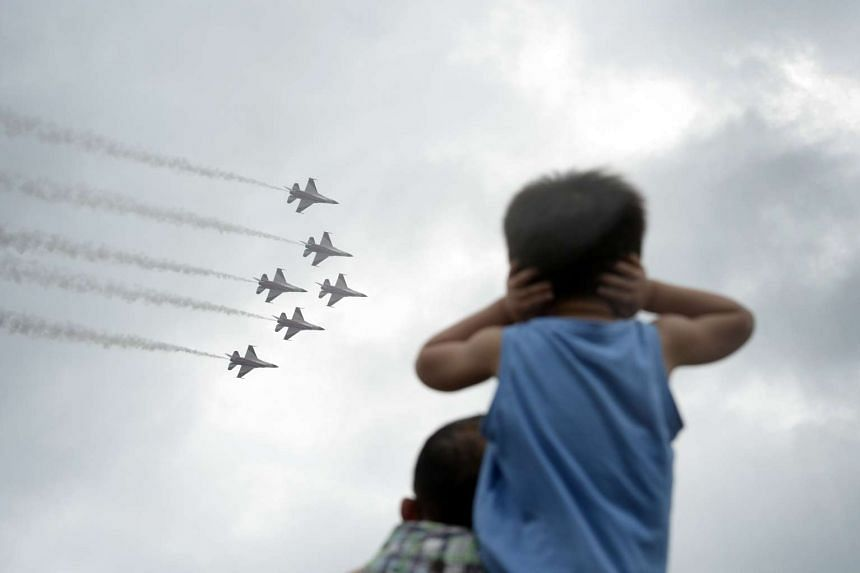 Families at the Marina Barrage to catch the Black Knights aerial display despite the intermittent heavy downpour.