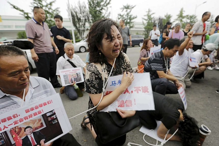 Relatives of passengers of Malaysia Airlines flight MH370, crying as they kneel down in front of media ahead of a briefing given by Malaysia Airlines, in Beijing.