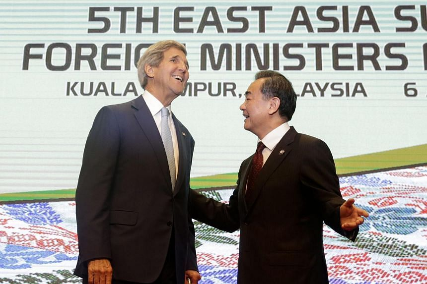 US Secretary of State John Kerry (left) with China's Foreign Minister Wang Yi (right) at the East Asia Summit in Kuala Lumpur, Malaysia, on Aug 6, 2015.