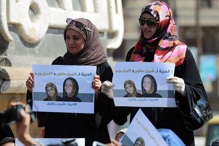 This March 5, 2015, file photo shows Yemeni women holding posters with pictures of French national Isabelle Prime (right) and her Yemeni interpreter Sherine Makkaoui (left) during a demonstration calling for their release in Sanaa.
