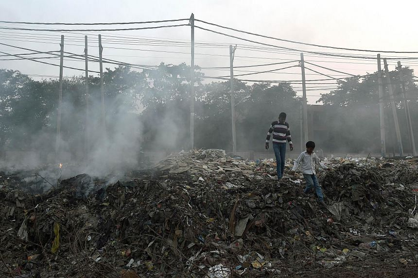 A man walking over a pile of burning garbage on the roadside in New Delhi.