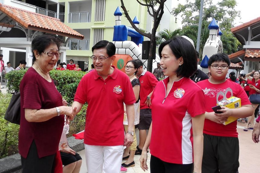 Tampines MPs Irene Ng (second from right) and Heng Swee Keat (third from right) interacting with residents during a National Day Family Carnival at Tampines Changkat on Aug 7, 2015.