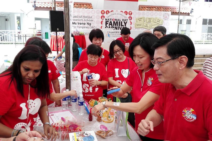 Tampines MPs Irene Ng (second from right) and Heng Swee Keat (right) interacting with residents during a National Day Family Carnival at Tampines Changkat on Aug 7, 2015.
