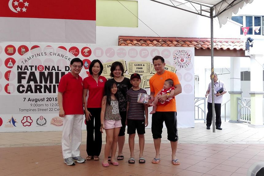 Tampines MPs Irene Ng (second from left) and Heng Swee Keat (left) interacting with residents during a National Day Family Carnival at Tampines Changkat Aug 7, 2015.
