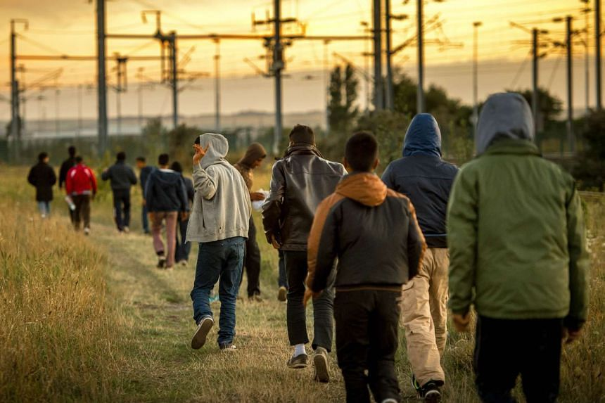 Migrants walk in the direction of the Eurotunnel terminal on Aug 6, 2015.