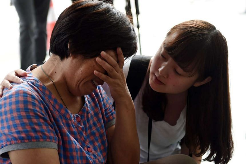 A relative of an MH370 passenger is consoled by a journalist outside Malaysia Airlines' office in Beijing on Aug 6, 2015.