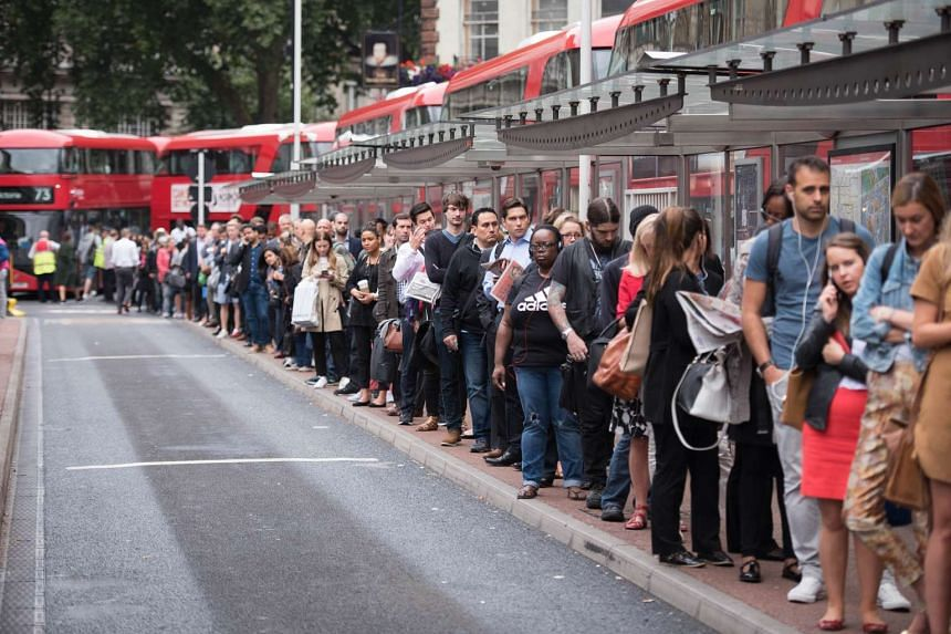 Commuters queue for buses as a 24-hour tube strike hits the morning rush hour at Victoria station, central London.