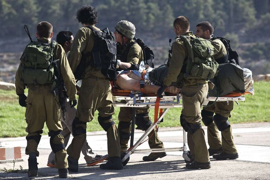 A wounded man is carried out of an Israeli Air Force helicopter,  one of the three Israelis who were deliberately run down.